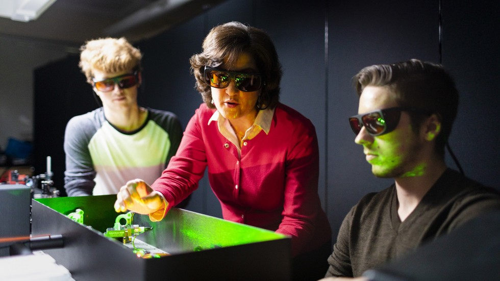 Students work with professor on laser equipment