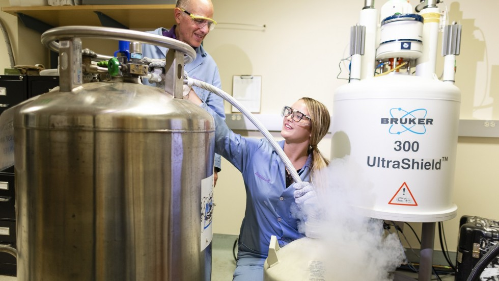 Student works with professor on NMR Machine