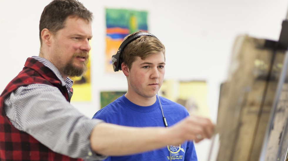 Photo of Shane Savage-Rumbaugh,  professor of Visual & Performing Arts working with student