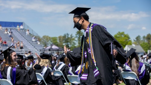Outgoing Student Government Association President Abe Medeiros '21 high fives a fellow graduate after receiving his diploma.