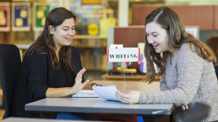 Two girls smiling with a notebook between them.